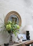 Decoraci?n decorativa de la pared: un espejo, una consola con una l?mpara, flores y baratijas foto de archivo libre de regalías