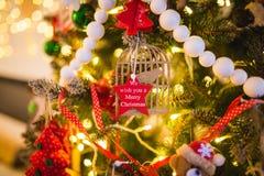 Decoración del Año Nuevo bajo la forma de estrella roja en un árbol de navidad con la inscripción le deseamos una Feliz Navidad Foto de archivo libre de regalías