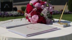 Decoración del arco de la boda con la tabla del registro para los recienes casados con las flores violetas y púrpuras La sol ilum almacen de metraje de vídeo