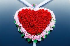 Decoración del coche de la boda como corazón de rosas rojas Imagenes de archivo