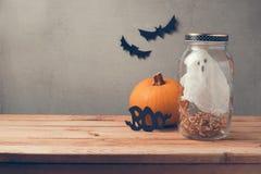 Decoración del día de fiesta de Halloween con el fantasma en tarro y calabaza anaranjada en la tabla de madera Foto de archivo
