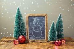 Decoración del día de fiesta de la Navidad con el dibujo de la pizarra y del muñeco de nieve en la tabla de madera Fotografía de archivo