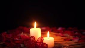 Decoración del día de San Valentín de la cantidad con la quema y pétalos de la vela