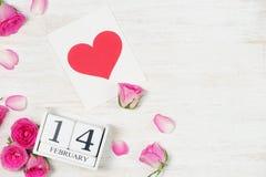 Decoración del día del ` s de la tarjeta del día de San Valentín con las flores y el bloque de calendario color de rosa Foto de archivo libre de regalías
