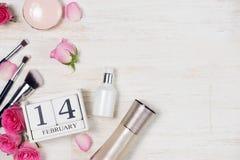 Decoración del día del ` s de la tarjeta del día de San Valentín con las flores y el bloque de calendario color de rosa Foto de archivo