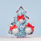 Decoración del hogar de la Navidad - abeto decorativo rojo brillante y bolas de plata con los arcos de seda rojos en el fondo bla fotos de archivo libres de regalías