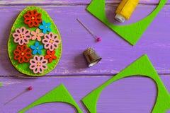 Decoración del huevo del fieltro de la flor El huevo de Pascua del fieltro con las flores de madera multicoloras abotona Pedazo d Fotos de archivo