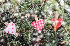 Decoración del invierno con los corazones rojos en árbol de abeto de Navidad Imagenes de archivo