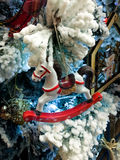 Decoración del juguete del caballo en una rama de árbol de navidad con nieve artificial Imagen de archivo libre de regalías