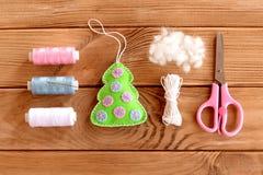 Decoración del ornamento del árbol de navidad del fieltro en una tabla de madera Idea de la Navidad DIY Fotos de archivo