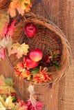 Decoración del otoño con una cesta de madera y hojas y manzanas de arce Imágenes de archivo libres de regalías