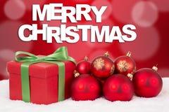 Decoración del regalo de la tarjeta de la Feliz Navidad con las bolas rojas Foto de archivo libre de regalías