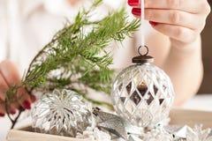 Decoración del tiempo de la Navidad en mano femenina Imagen de archivo libre de regalías