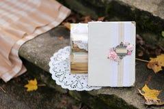 Decoración elegante lamentable y hojas de otoño caidas Libro blanco del vintage con el lugar para el texto en los pasos de piedra Foto de archivo libre de regalías