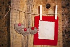Decoración en fondo de madera con el corazón de la tela y la tarjeta en blanco Fotos de archivo