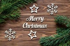 Decoración en la tabla de madera con los copos de nieve, estrellas, inscripción de la Feliz Navidad Foto de archivo