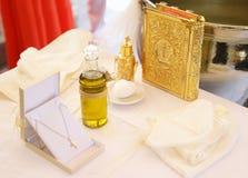 Decoración griega ortodoxa del bautizo - aceite del bautismo, cruz y el nuevo testamento fotografía de archivo