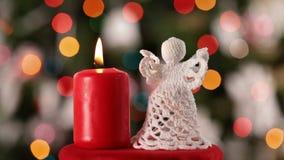 Decoración hecha a ganchillo del ángel de la Navidad y vela ardiente almacen de metraje de vídeo