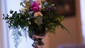 Decoración hermosa de la boda hecha de flores de diferentes tipos y de colores en una tabla de la boda en un restaurante de lujo almacen de metraje de vídeo