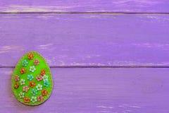 Decoración hermosa del huevo de Pascua con las gotas florales plásticas Huevo creativo del fieltro aislado en fondo de madera púr Imágenes de archivo libres de regalías