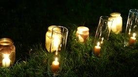 Decoración hermosa para una ceremonia de boda nocturna, tarros del vintage con las velas metrajes