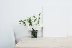 Decoración interior blanca, flores naturales frescas en florero y lona foto de archivo