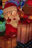 Decoración ligera colorida de Santa Claus que aumenta su pulgar para arriba que parece feliz con las pilas de cajas de regalo Fotos de archivo