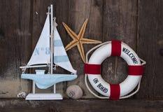 Decoración marítima con las cáscaras, estrellas de mar, velero, red de pesca en la madera azul de la deriva foto de archivo libre de regalías