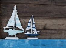 Decoración marítima con las cáscaras, estrellas de mar, velero, red de pesca en la madera azul de la deriva fotografía de archivo libre de regalías