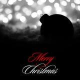 Decoración misteriosa de la Navidad con la bola negra en la nieve en el fondo de las luces borrosas blanco del día de fiesta Tarj Fotos de archivo