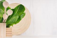 Decoración moderna de la cocina - el plato de madera beige, cucharas, verde se va en el fondo de madera blanco de la luz suave imágenes de archivo libres de regalías