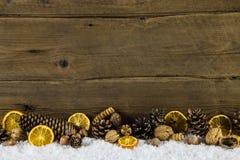 Decoración natural de la Navidad con las naranjas, las nueces y el cono de abeto encendido Imagenes de archivo