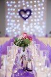 Decoración púrpura de la tabla de la boda con el foco en la pieza central de la flor Foto de archivo libre de regalías
