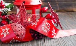 Decoración roja de la Navidad con la estrella del brillo, la linterna y la cinta festiva Foto de archivo