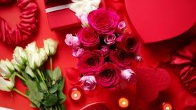 Decoración romántica de día de San Valentín con las rosas, regalos encajonados, velas