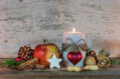 Decoración romántica de la Navidad con la luz de la vela, la galleta de la estrella, las especias rojas de la manzana, nuts y aro Foto de archivo