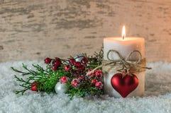 Decoración romántica de la Navidad o del advenimiento con la vela, el corazón y la nieve Fotografía de archivo libre de regalías