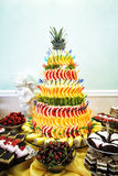 Decoración, tortas y galletas de la pirámide de la fruta en la tabla del postre en Foto de archivo