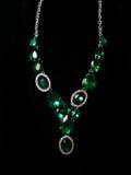 Decoración verde de las piedras del collar en un fondo negro imágenes de archivo libres de regalías