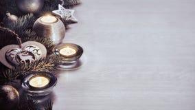 Decoración y vela de la Navidad en el tablero de madera Imagen de archivo