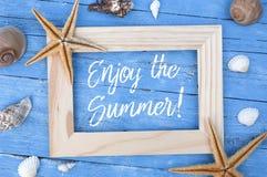 Decoraci?n mar?tima con los pescados de la estrella, c?scaras en la madera resistida azul con lema disfrutar del summe fotos de archivo