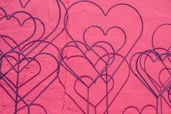 Decoración de los corazones en una pared violeta Fotografía de archivo libre de regalías