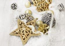Decoraciones brillantes de oro de la Navidad del vintage en la nieve con Eleg Foto de archivo libre de regalías