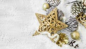Decoraciones brillantes de oro de la Navidad en la nieve con Ribb elegante Foto de archivo libre de regalías