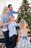 Decoraciones colgantes de la familia en un árbol de navidad Fotos de archivo