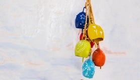 Decoraciones coloridas que cuelgan en una pared blanca foto de archivo