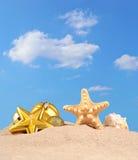 Decoraciones, conchas marinas y estrellas de mar de la Navidad en una arena de la playa Fotos de archivo libres de regalías