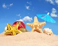 Decoraciones, conchas marinas y estrellas de mar de la Navidad en una arena de la playa Imagen de archivo
