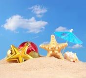 Decoraciones, conchas marinas y estrellas de mar de la Navidad en una arena de la playa Imagenes de archivo