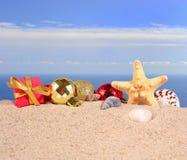 Decoraciones, conchas marinas y estrellas de mar de la Navidad en una arena de la playa Fotos de archivo